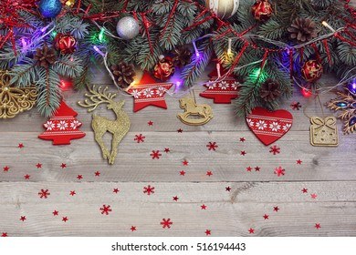 Christmas background with fir branches, Christmas decorations and confetti.