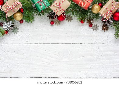 Christmas background with fir branches, decorations, gift boxes and pine cones on white wooden table. Christmas background. Flat lay. top view with copy space