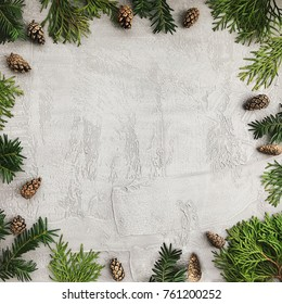 Christmas background with fir branches and pine cones. Floral New Year frame. Border with copy space.