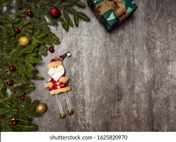 Christmas background. Fir branches with fir tree toys on the concrete background. Top view. Holiday concept