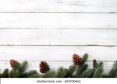 Christmas background - fir leaves and pine cones decorating rustic elements on white wood table. Creative Flat layout and top view composition with border and copy space design.