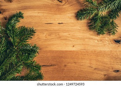 Christmas background with fir spruce tree, blank frame on brown wooden table. Top flat view with copy space.