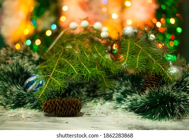 Christmas background with fir tree, balls, garlands. Blurred background with lights from Christmas lights. Cones and tinsel. Christmas tree. Holiday concept.
