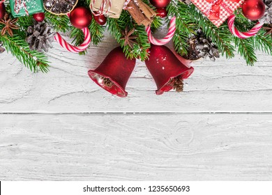 Christmas background with fir tree, christmas bells, candy, gift boxes, berries and pine cones on white wooden table with copy space for your text. top view. flat lay