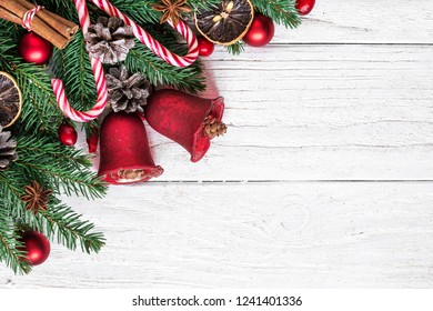 Christmas background with fir tree, christmas bells, candy, red berries and pine cones on white wooden table with copy space for your text. top view. flat lay