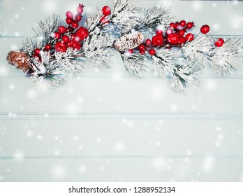 christmas background fir tree branch with cones and snow on wooden blue board