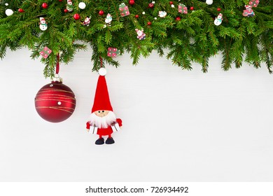 Christmas background. Christmas fir tree branch with Santa and red Christmas ball on white wooden background. Copy space, top view