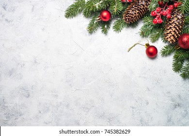 Christmas background. Fir tree branch and red christmas decorations on gray stone background. Top view with copy space.