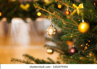 Christmas background with fir tree branches, Xmas decorations, and golden glass big and small balls with bow. Golden boke on background