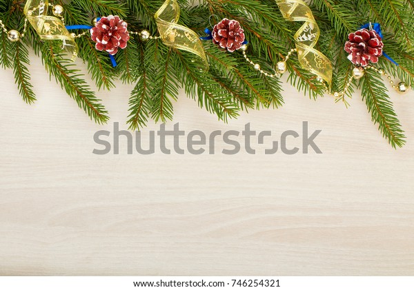 christmas background with fir tree branches, cones and ribbons on wooden background
