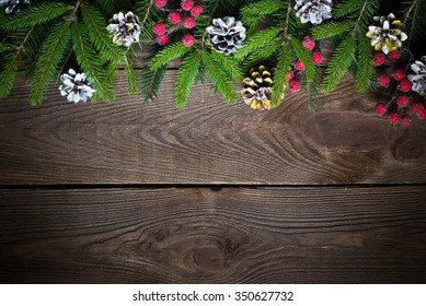 Christmas background with fir tree brunches and decorations at dark wooden table. Top view, copy space.