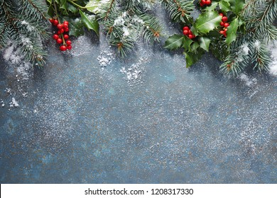 Christmas background with fir tree and holly berry on a blue stone background covered in snow with copy space.