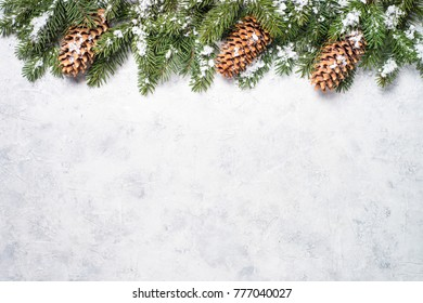 Christmas background. Christmas fir tree and pine cones on gray stone table. Top view with copy space.