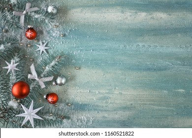 Christmas background with fir twigs, light green and red trinkets and silver stars on light abstract background with ltext space