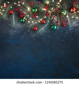 Christmas background with fir twigs, red berries, cones and Xmas lights on dark abstract background with plenty of text space