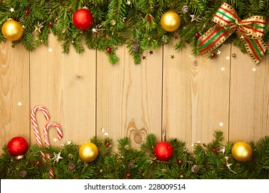 Christmas background with firt-ree, candies, baubles and stars on wood