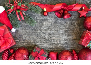 Christmas background frame decorations gift boxes with claus hat and red ribbon bow with ornament bauble on vintage wooden table with copy space flat lay style, Greeting card for new year