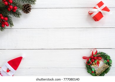 Christmas background. Christmas frame made of fir branches, holly berry and red gift box  with decoration on white wood board. Creative flat lay, top view design.