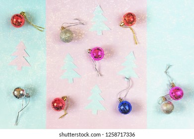Christmas background with free space for text. Flat lay. Christmas balls and paper fir-trees on colored paper background; bright festoon illumination - double exposure