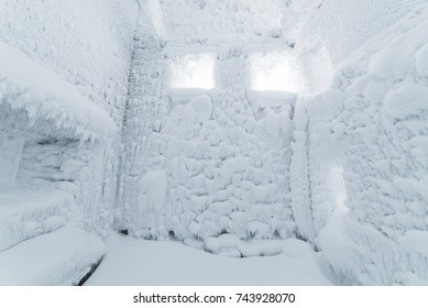 Christmas background from frost. Abstract winter texture for design. Hoarfrost and snow on the walls of the room with a windows
