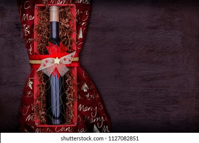 Christmas background with gift bottle of red wine or red liquor, which is festively packaged in red cardboard box tied with red and gold bow and gold star, on wooden background, top table, copy space.