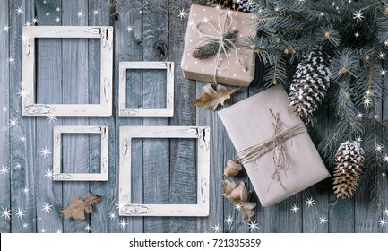 Christmas background with gift box and four photo frames in vintage style on wooden planks. New Year winter holidays concept. Empty place for photo or text. Copy space. Top view.