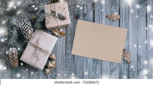 Christmas background with gift box and kraft eco paper in vintage style on wooden planks. New Year winter holidays concept. Empty place for photo or text. Copy space. Top view.