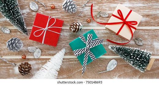 Christmas background with gift box and christmas tree  on wooden table from top view