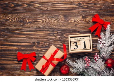 Christmas background with gift boxe in craft paper with red ribbon, Christmas decorations, wooden calendar with date 31 of december on rustic dark wooden background. Preparation for holidays. Top view