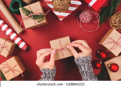 Christmas background with gift boxes, clews of rope, paper's rools and decorations on red. Preparation for holidays. Top view with copy space. Woman's hands holding gift box.