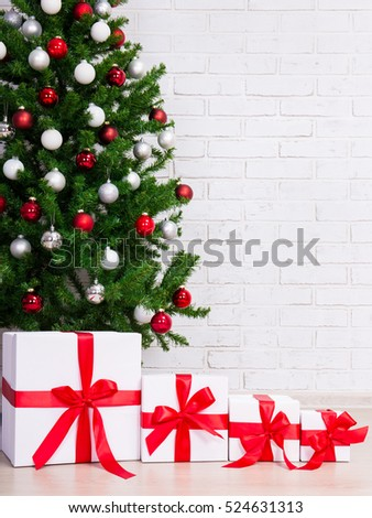 christmas background gift boxes under decorated christmas tree over brick wall