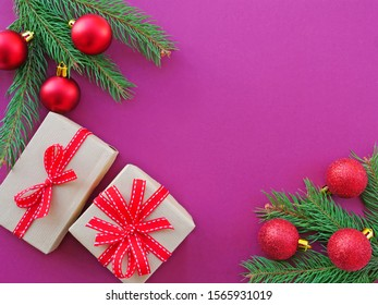 Christmas background with gift, fir branches and decorations over purple magenta background