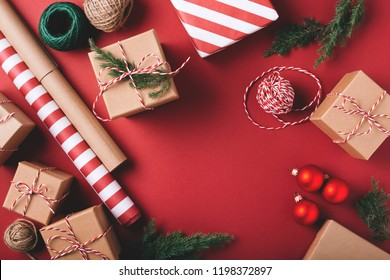 Christmas background with gifts and decorations on red. Preparation for holidays. Top view with copy space.