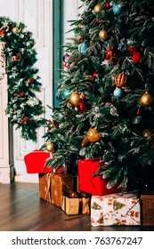 Christmas background: gifts under decorated Christmas tree by the fireplace