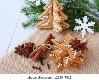 Christmas background with gingerbread figurines, cinnamon, star anise, cloves and fir branches over burlap on the table.