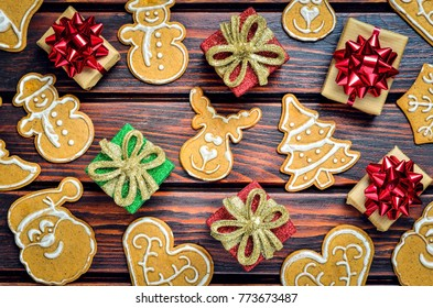 Christmas background with gingerbread. Sweet gingerbreads and gifts on a wooden table.