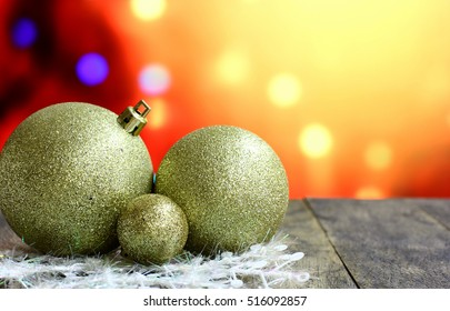 Christmas background with gold balls decorations on old dark wooden desk table. Colorful holiday bokeh garland lights. Wood foreground and ready for product montage. Light copyspace on top corner.