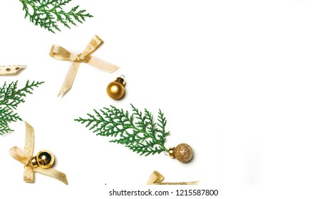 Christmas background with golden decorations put as frame isolated on white with fir branches. Bright and festive flat lay. Top view, Copyspace for text. Greetings for christmas or new year.