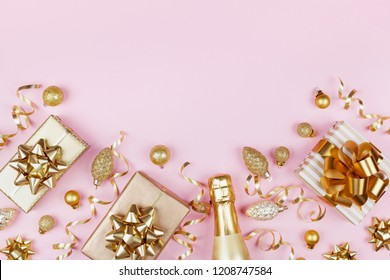 Christmas background with golden gift or present box, champagne and holiday decorations on pink pastel table top view. Greeting card with space for text. Flat lay style.