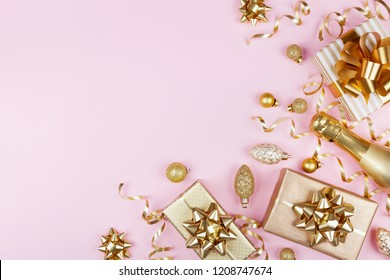 Christmas background with golden gift or present box, champagne and holiday decorations on pink pastel table top view. Greeting card with space for text. Flat lay.
