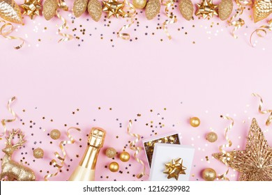 Christmas background with golden gift or present box, champagne and holiday decorations on pink pastel table top view. Greeting card. Flat lay style.
