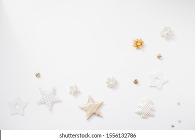Christmas background. Golden stars, bells and bows on white background. Flat lay, top view, copy space