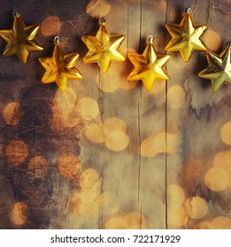 Christmas background with  golden  stars and christmas light over dark rustic wooden boards
