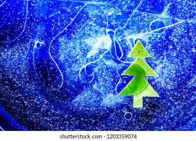 Christmas background. Green paper fir tree under frozen water