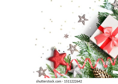 Christmas background, green pine branches, cones and gift box on white background. Creative composition with copy space, top view. New Year's holiday, christmas, decoration.
