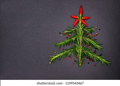 Christmas background with green Rosemary twigs as Christmas tree, red hot chili peppers as Christmas star on slate background.  Copy space,  text place