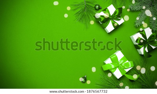 Christmas background green. White gift box with emerald ribbon, New Year balls and sparkling lights in xmas composition on dark green background for greeting card. Flat lay, top view, copy space.