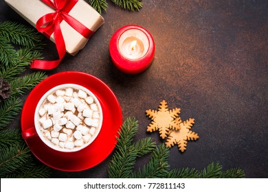 Christmas background or greeting card.  Christmas present, candle, fir tree and hot chocolate with marshmallow on rusty stone table. Top view with copy space.