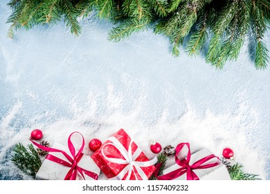 Christmas background for greeting card, with Christmas tree branches, decoration and gifts boxes with ribbons, on white background top view copy space for text
