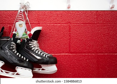 Christmas background of hockey skates with elf hanging over red wall with copy space